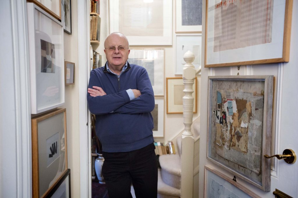 a photo of a man leaning against the door jamb of a corridor lined with paintings and prints