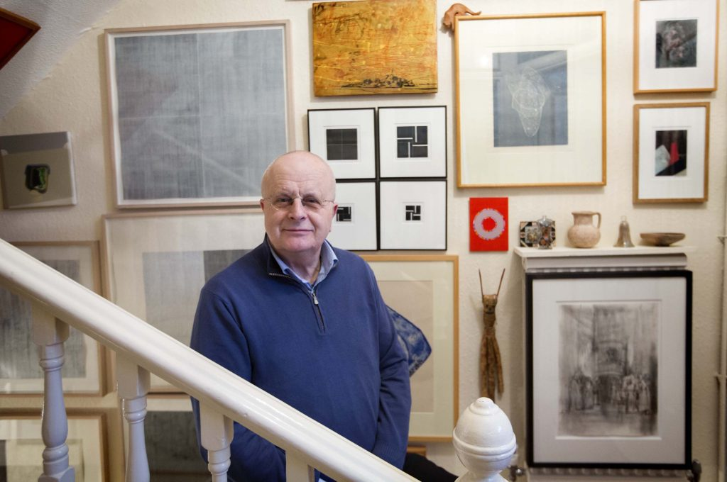 a photo of a man at the foot of a stairway with walls covered in artworks