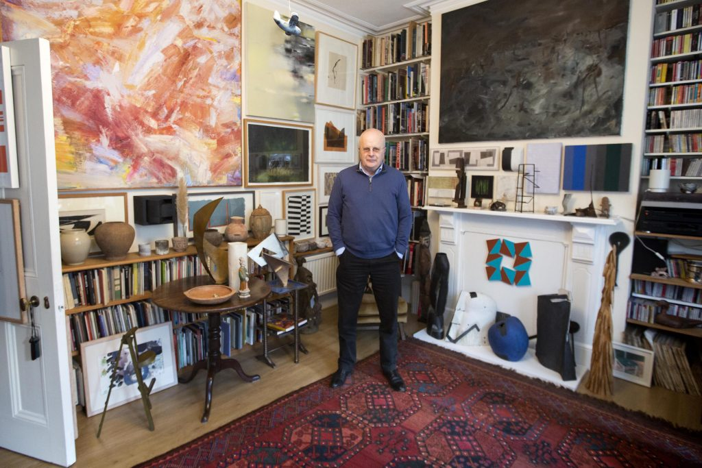 a photof of a man lined with books and artworks inlcuding paintings and sculpture