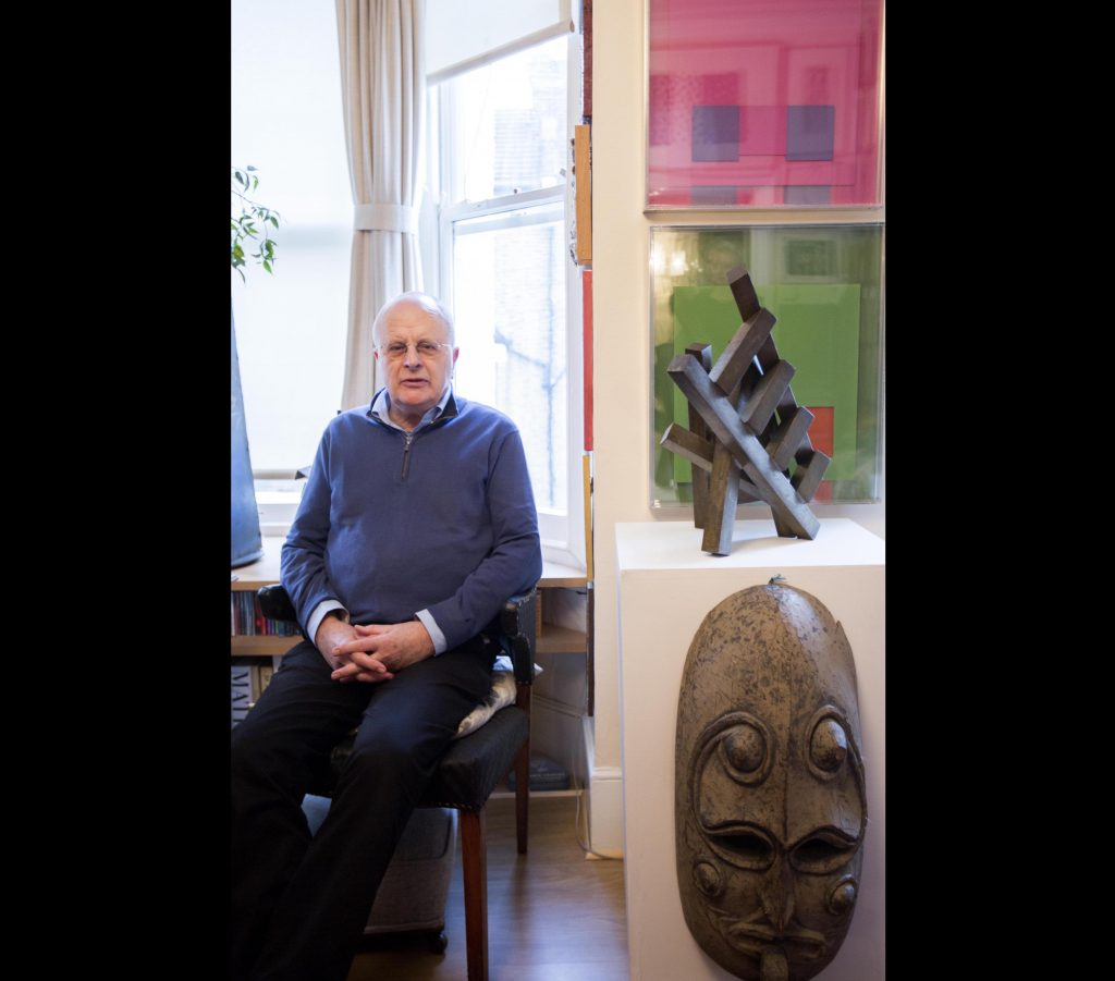 a photo of ma seated in a window next to artworks and an African mask
