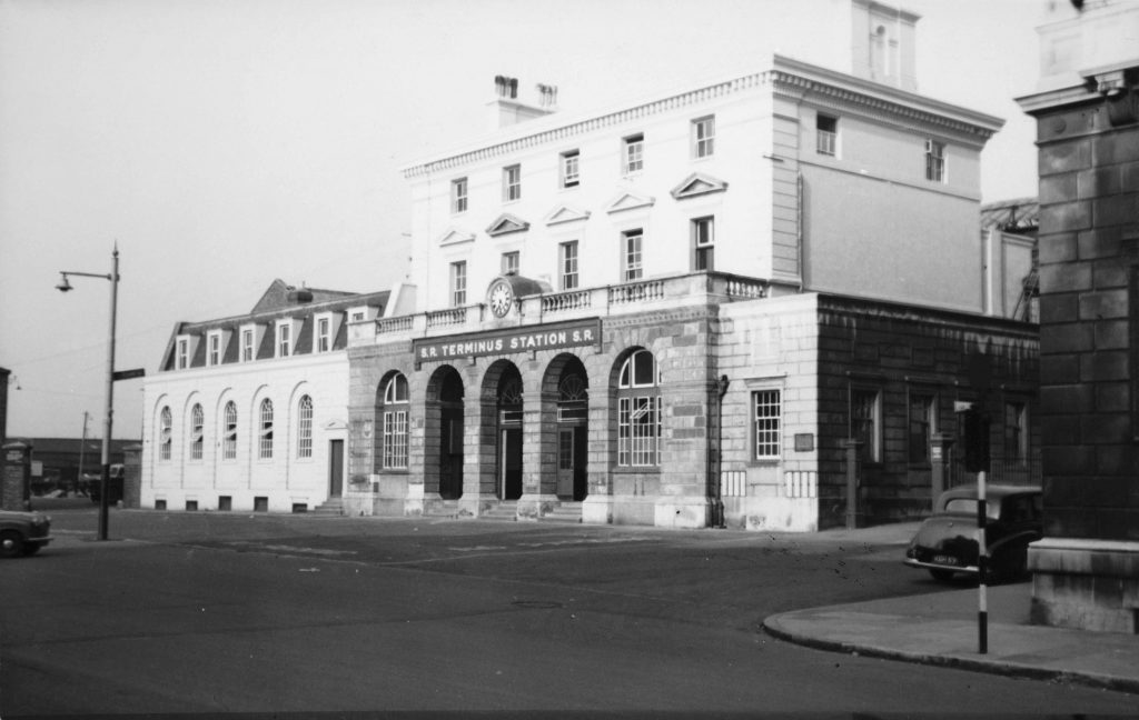 a black and white photo of a large building with an archway frontage
