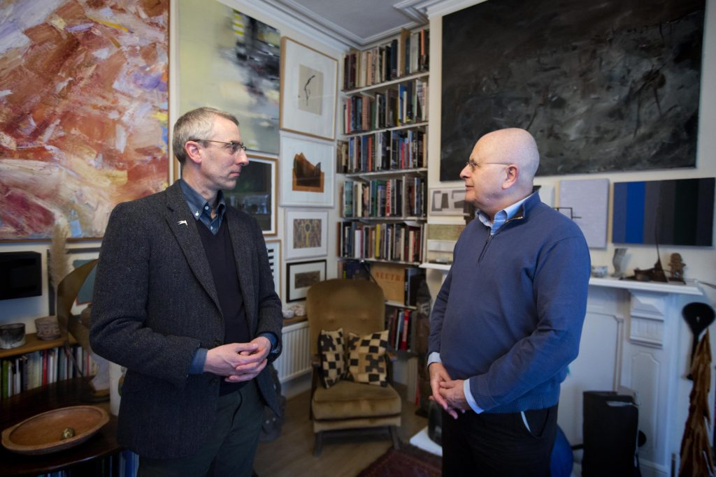 a photo of two men looking at each other in a roon filled with paintings