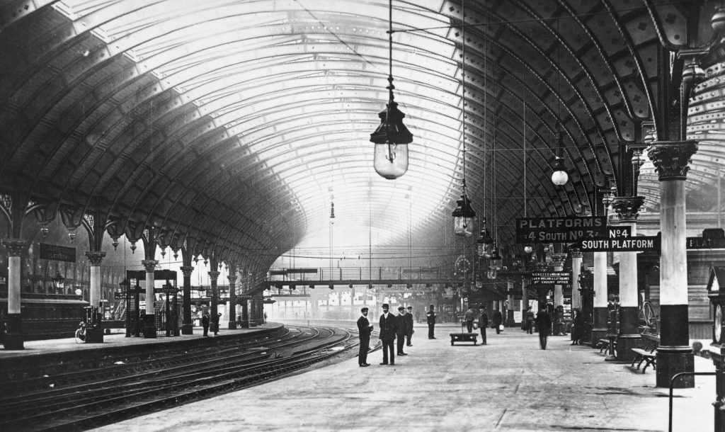 a black and white photo of a station platform with men in the distance