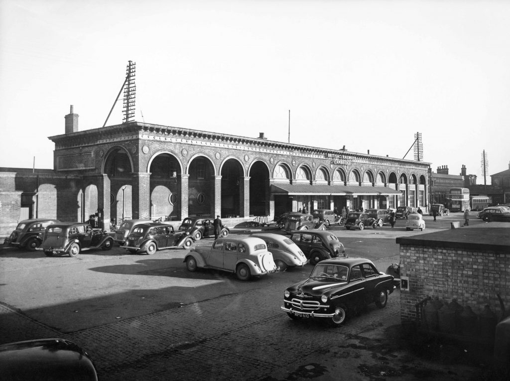 a photo of a railway station with cars parked outside