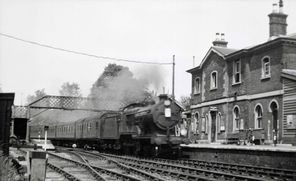 a photo of a train steaming through a railway station