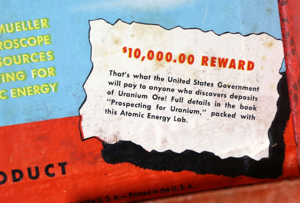 a text panel from a board game offering $10,000 U.S government reward for anyone discovering uranium.