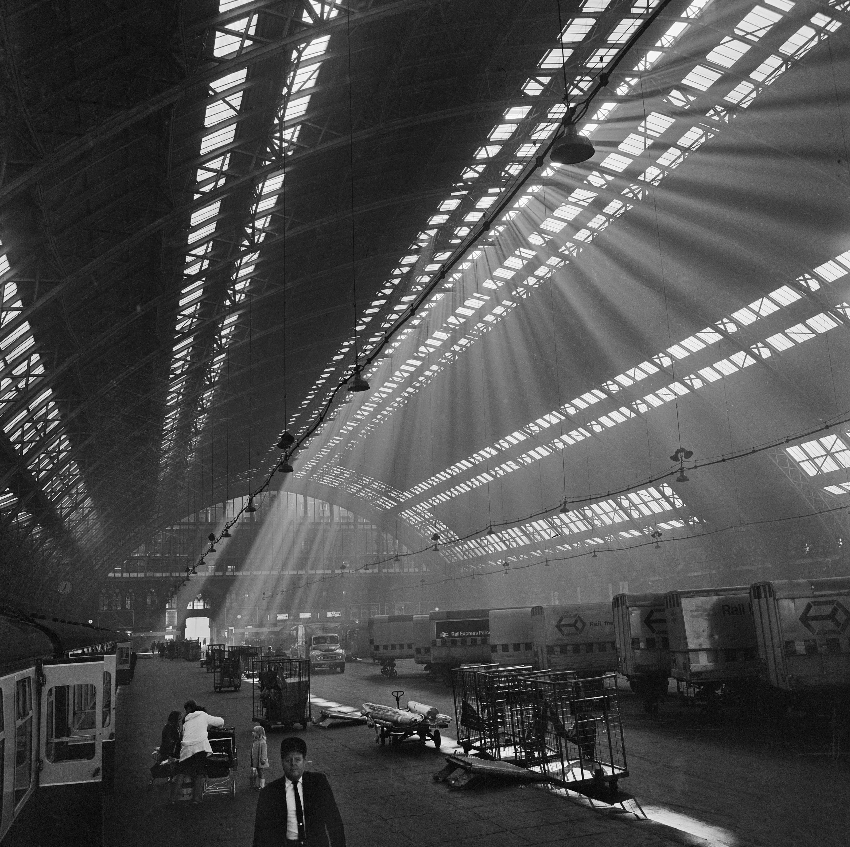 a black and white photo of railway station with shafts of light coming through the roof