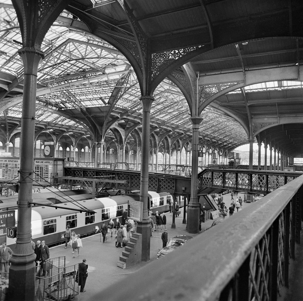 a black and white photograph of a railway station interior