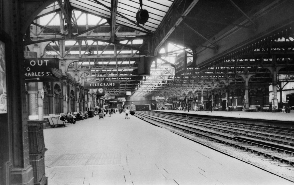 a black and white photo of a long station platform