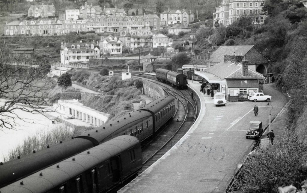 a black and white photo of a train next to a curved railway platfrom