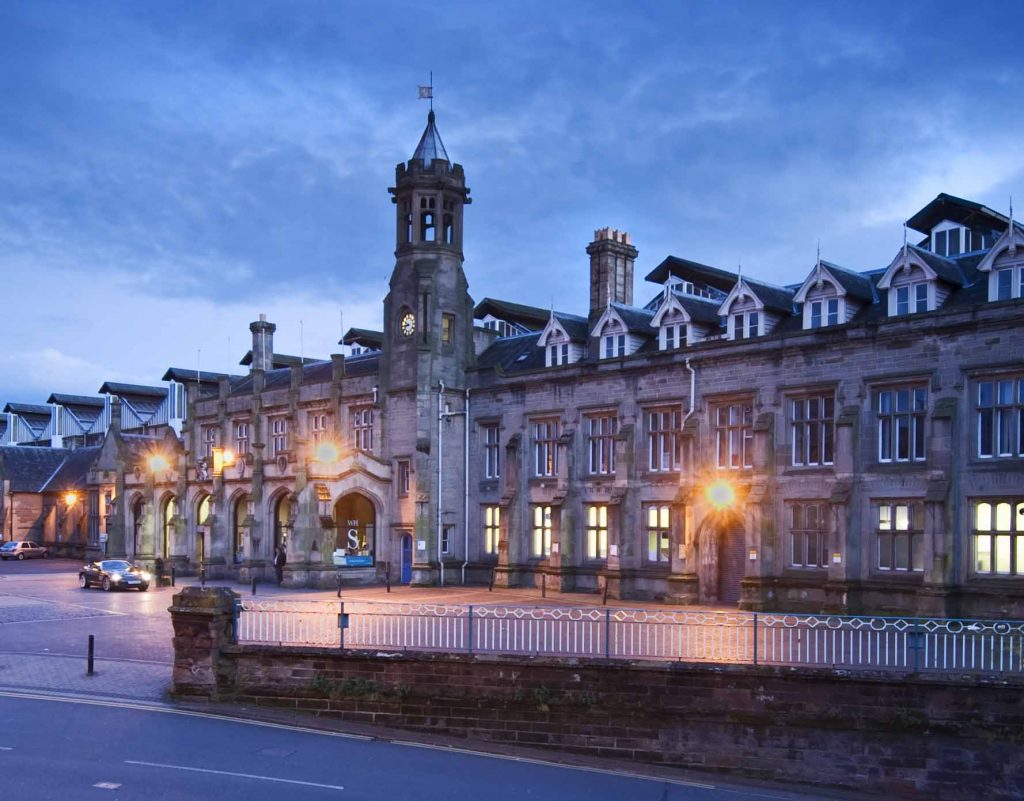 a colour photo of a railway station frontage at night