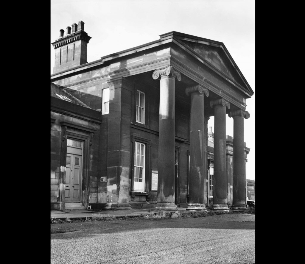 a black and white photo f large building with portico entrance