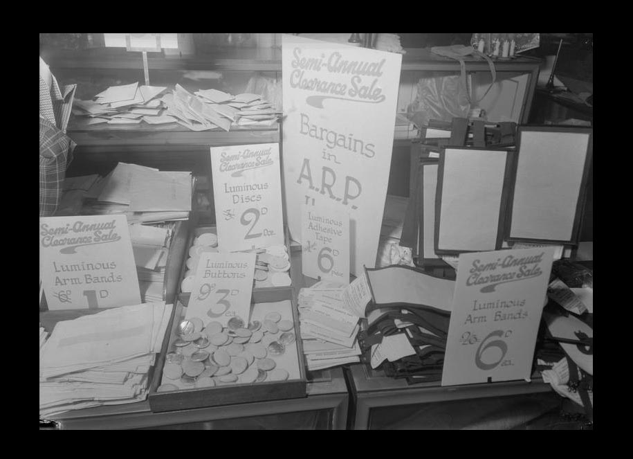 a photograph of a displkay in shop with signs saying ARP bargains with trays of luminous badges etc
