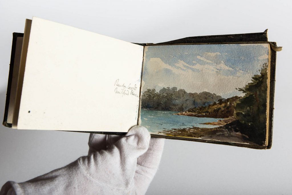 a photo of an open sketchbook showing a painted view of a lake