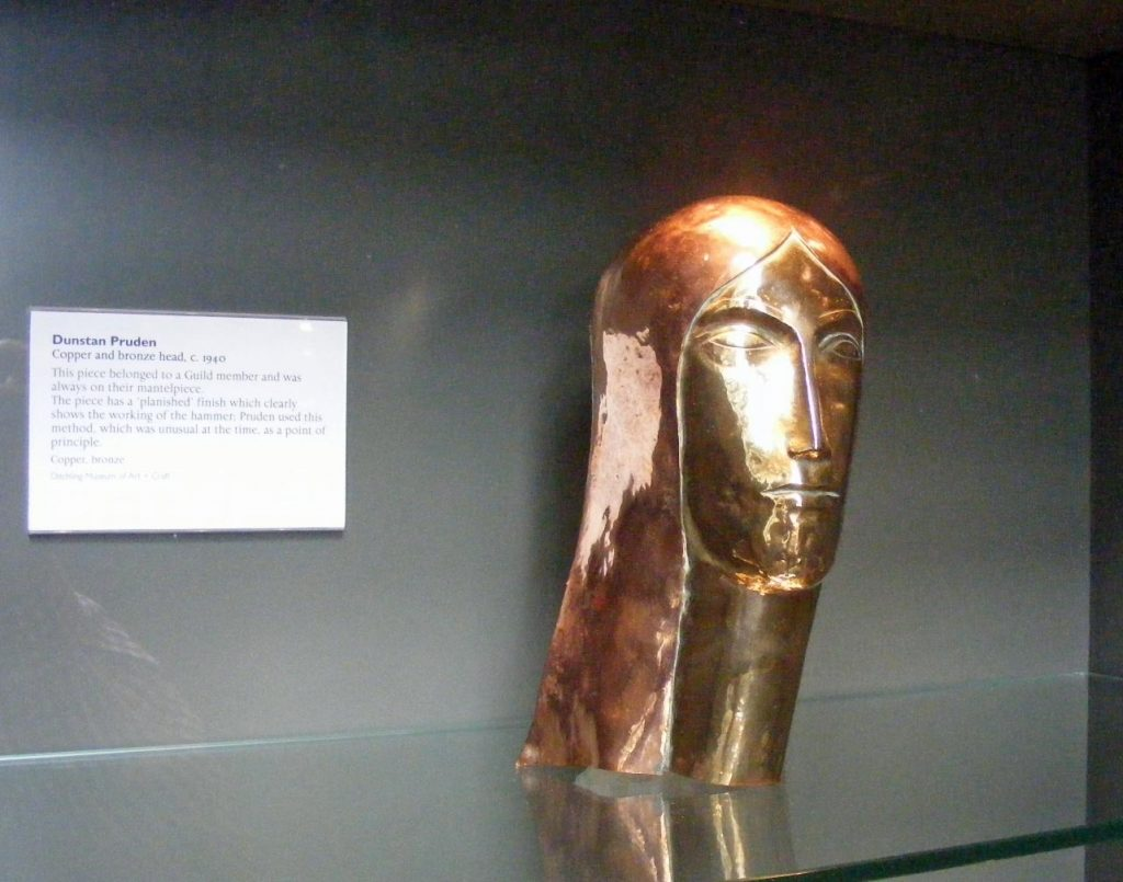 a photo of a carved bronze head in a display case