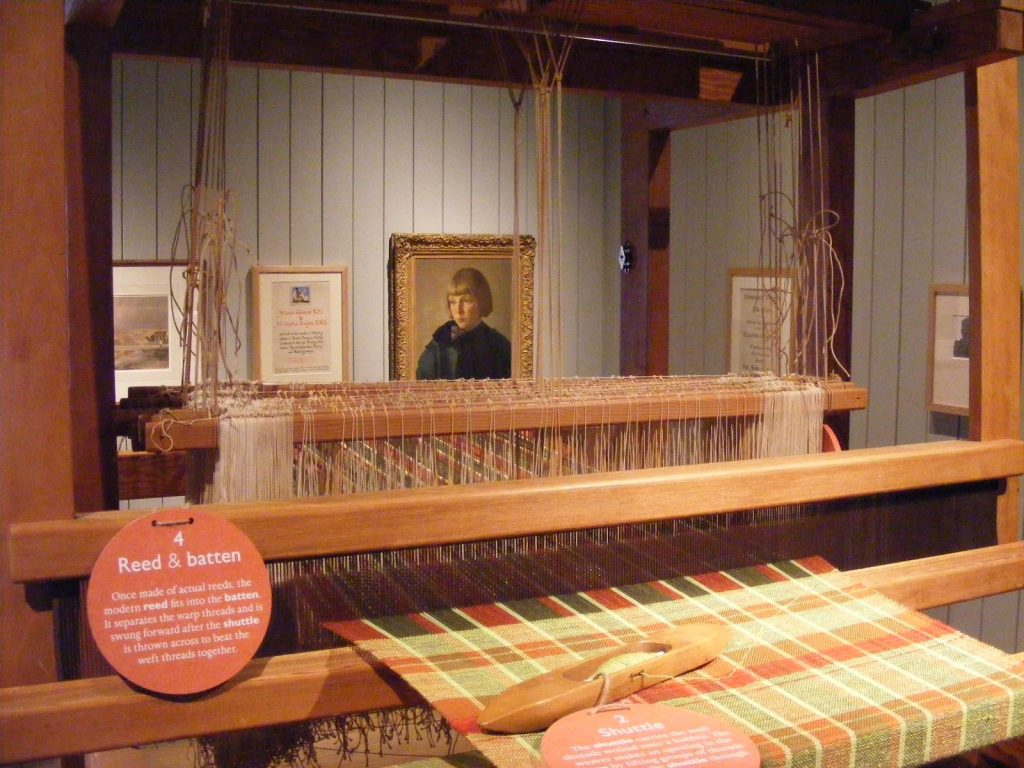 a photoof gallery with a female portriat seen through a reed and batton loom
