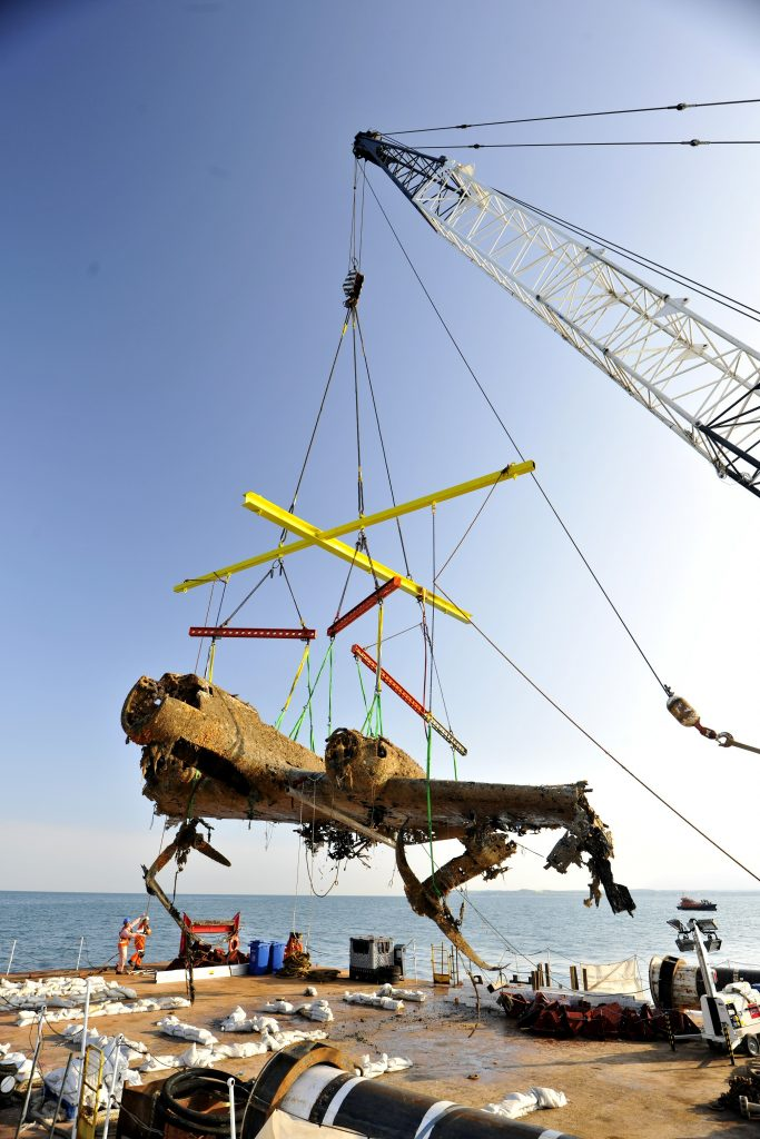 a photo of the wrekcage of a plane bening hosited on board a barge with a crane