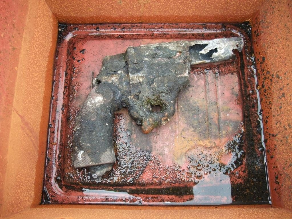 A photo of a rusted gun in a tray