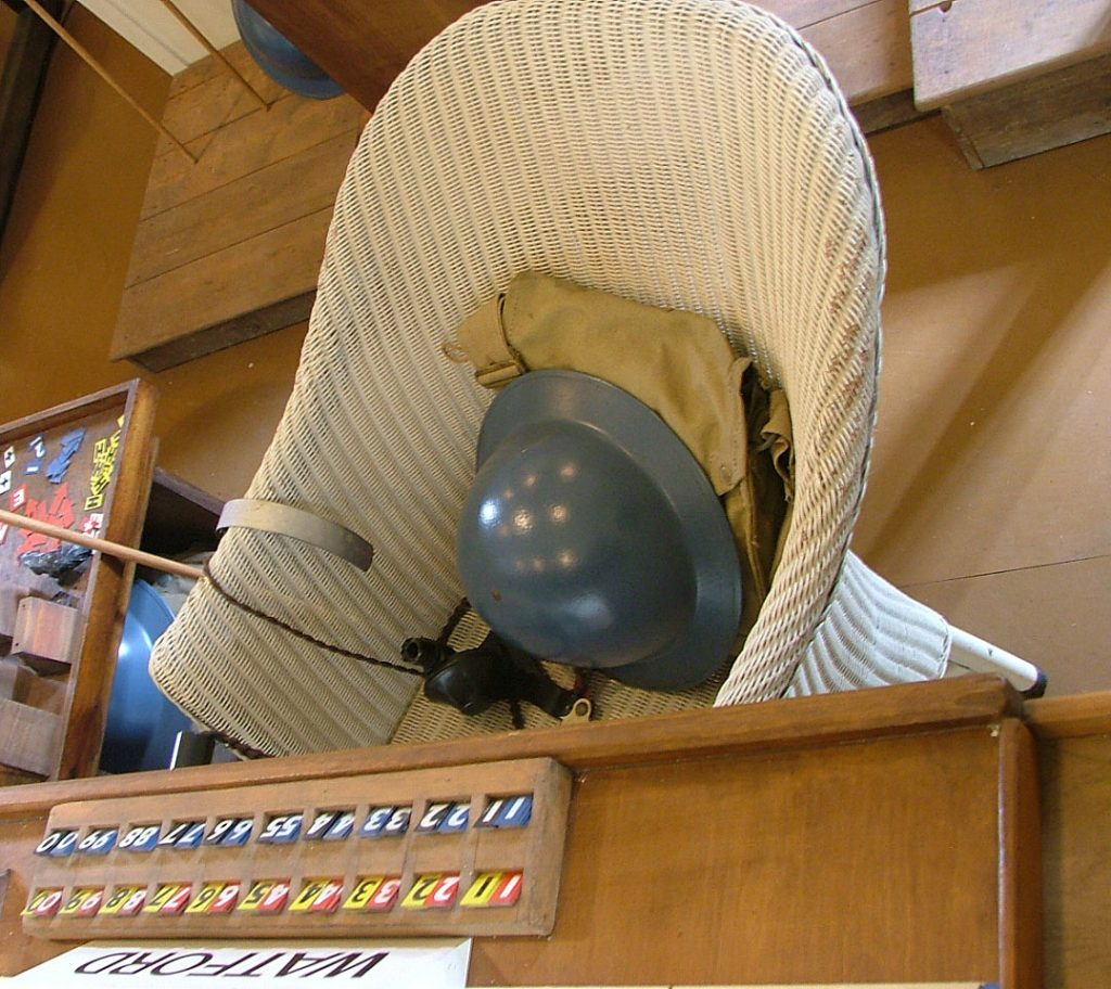 a photo of wicker chgair wih a grey tin helmet and bag resting on it