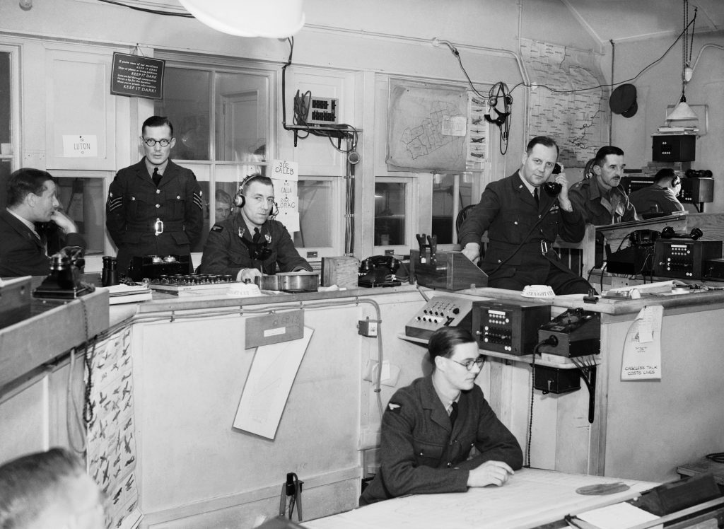 a black and white photo of a Battle of Britain ops room with men in position on the phone and wearing headphones