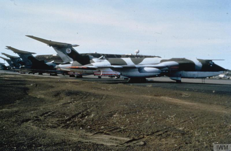 a photo of large camouflaged jet planes parked on a makeshift runway