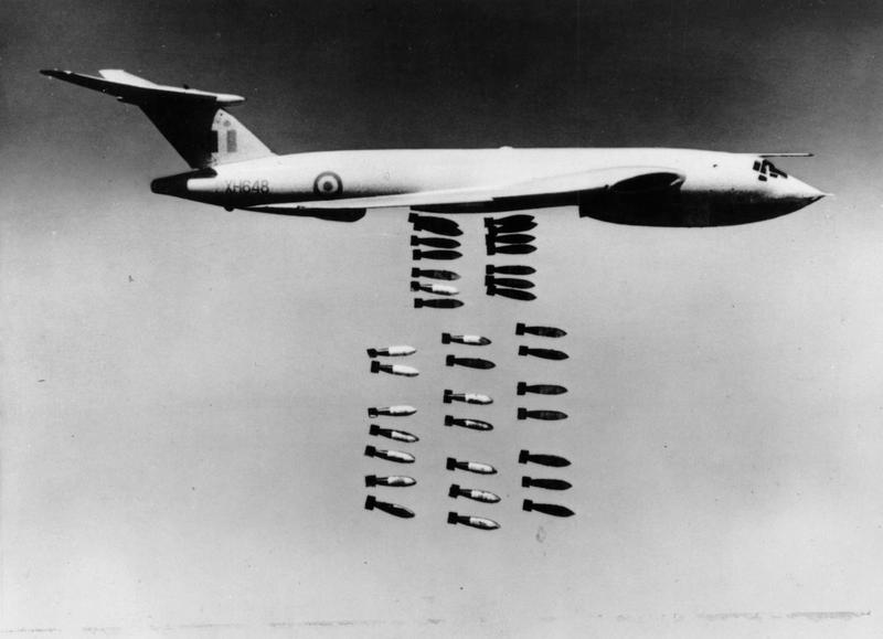 a black and white photo of a bomber dropping its payload of bombs