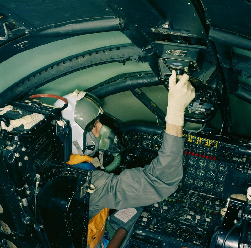 a photo of a pilot reaching up to a switch in a crowded cockpit