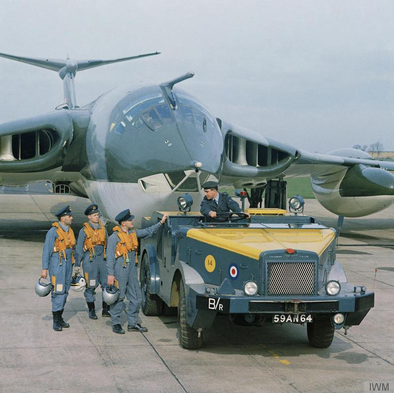 a photo of men talking to the driver of a truck which is towing a large jet plane