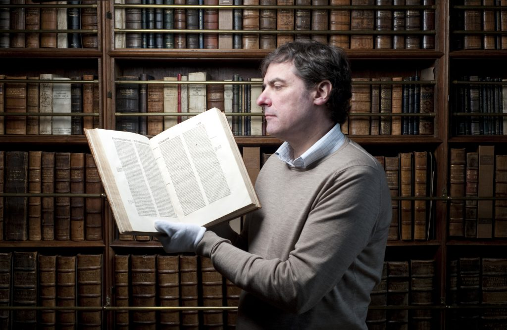 a photo of a man holding a book open in a library