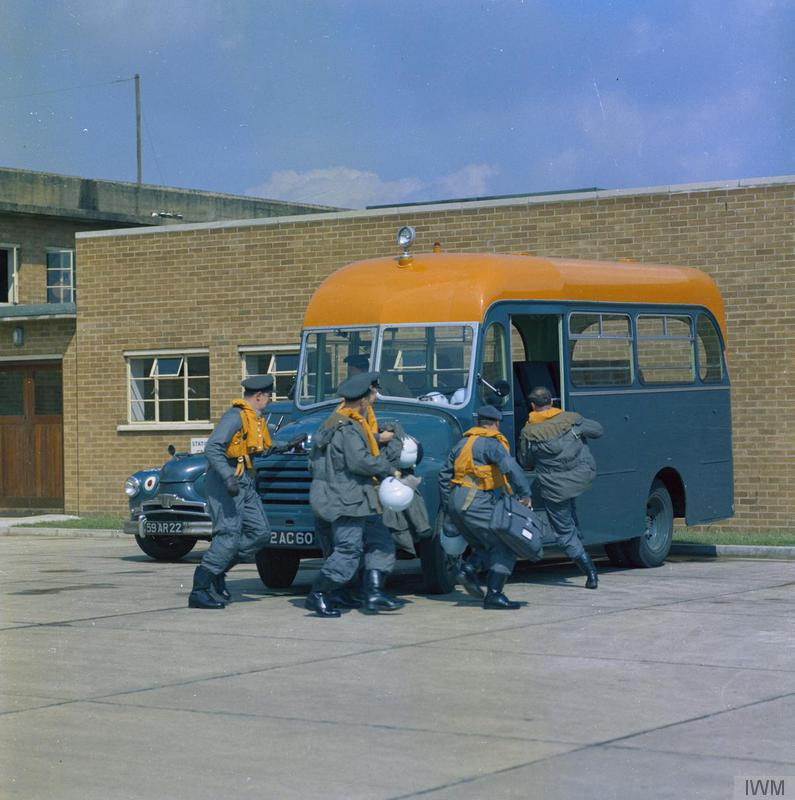 a phot of a group of RAF men runing to board an old fashioned looking bus