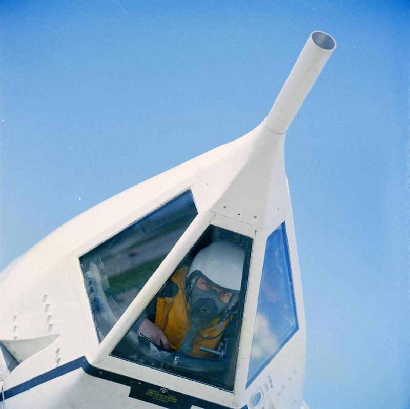 a photo of a cew member of an RAF jet bomber peering through a glass in the nose cone