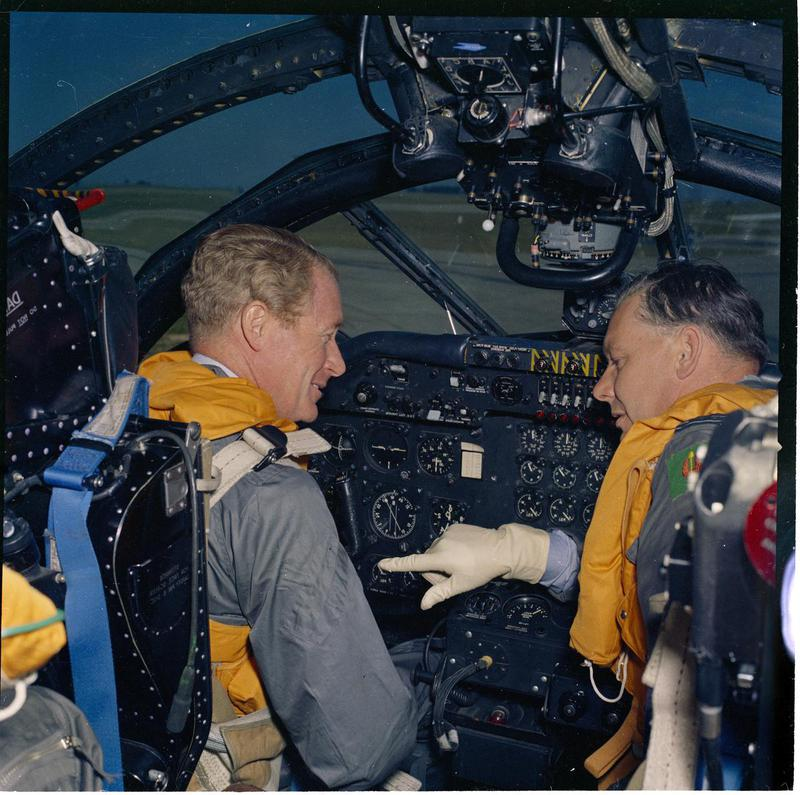 a phot of two men in a lrage cockpit area of a plane surrounded by dials