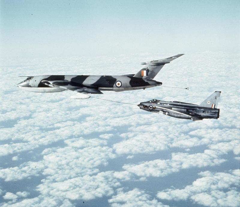 a phot of a sliver het fighter taking fuel from an umbilical pipeline of a larger plane