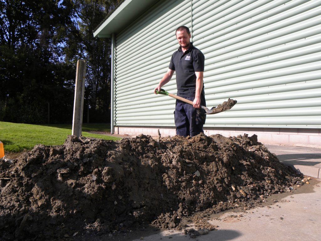 a phot of a man with shovel and large pile of mud and sand