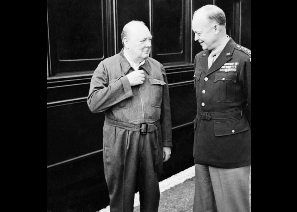 Winston Churchill with his hand on a zip of his utility siren suit next General Eisenhower in full military dress