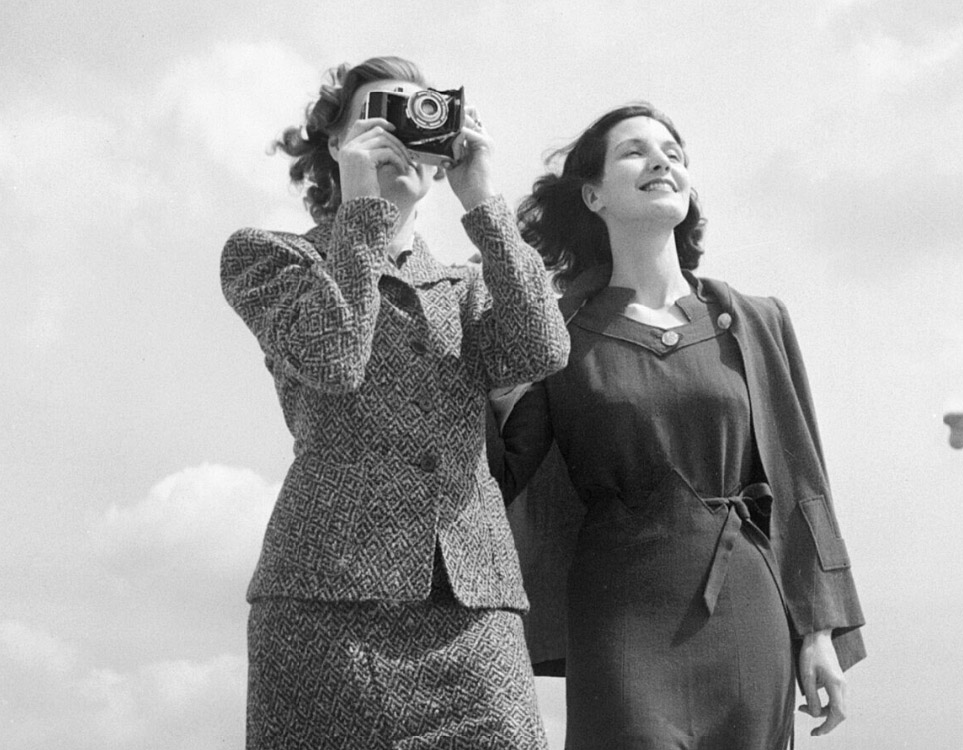 a photo of two models on a rooftop wearing tweed and wool suits with skirts