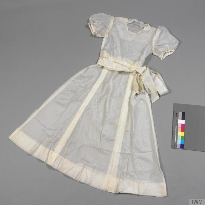 a photo of a small white dress with short sleeves and a white waist sash