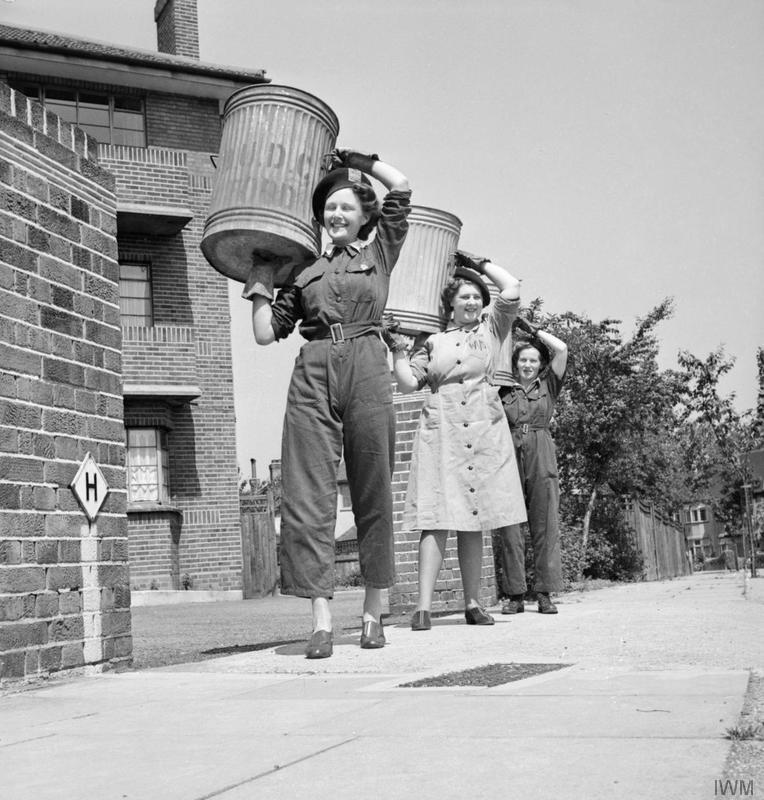 a photo of three women walking down a street with large pig bins on their shoulders
