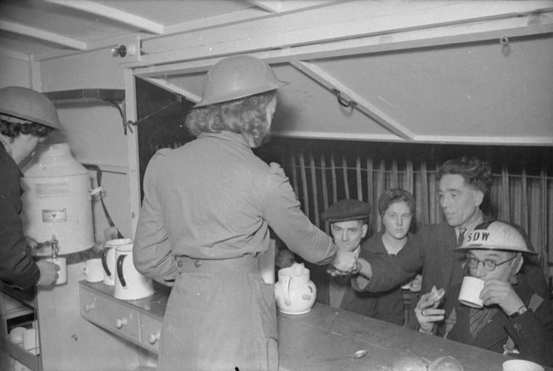 a photo of two women wearing british helmets serving tea from within a mobile canteen