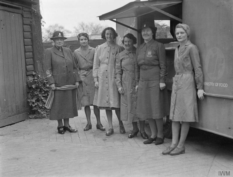 A photo of five women in smocks photographed in front of a mobile canteen