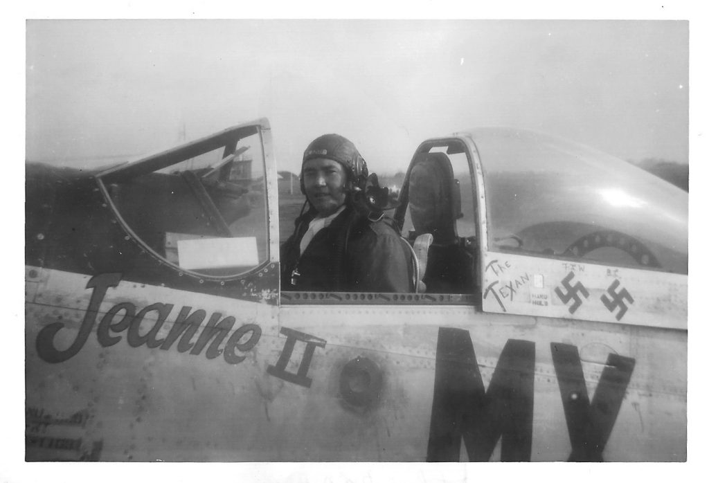 a black and white photo of a man in the cockpit of a Mustang fighter