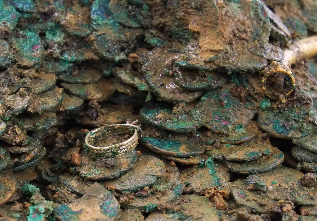 a photo a gold ring sitting within a hoard of coins
