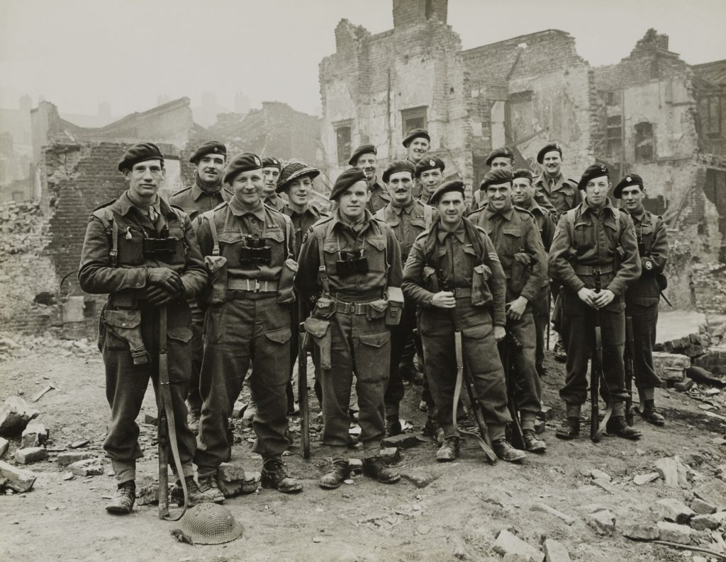A black and white photo of a group of Commandos standing with their weapons amidst the rubble of London