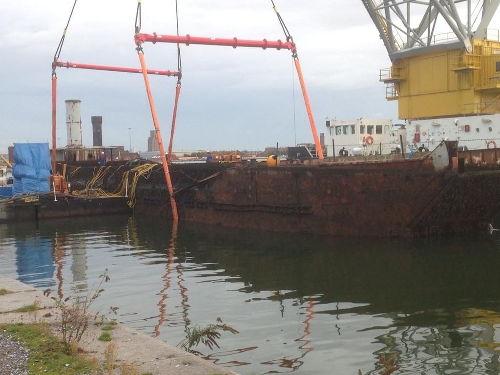 a photo of a large rusty craft in a dockside