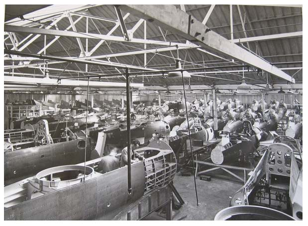 a photo of a factory with the fuselages of many planes