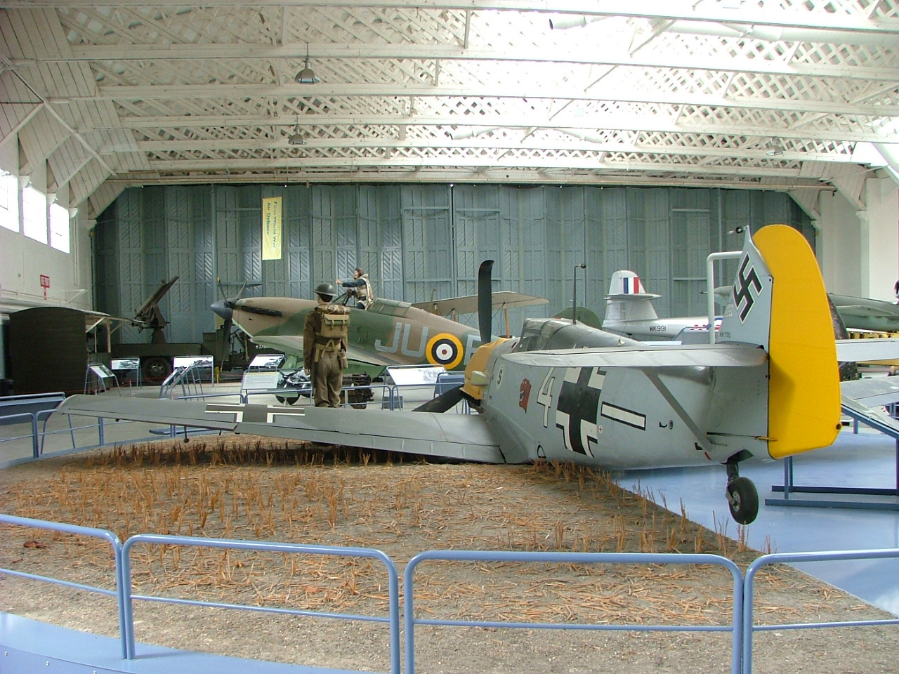 A photo of large hangar with aircraft displayed within it.