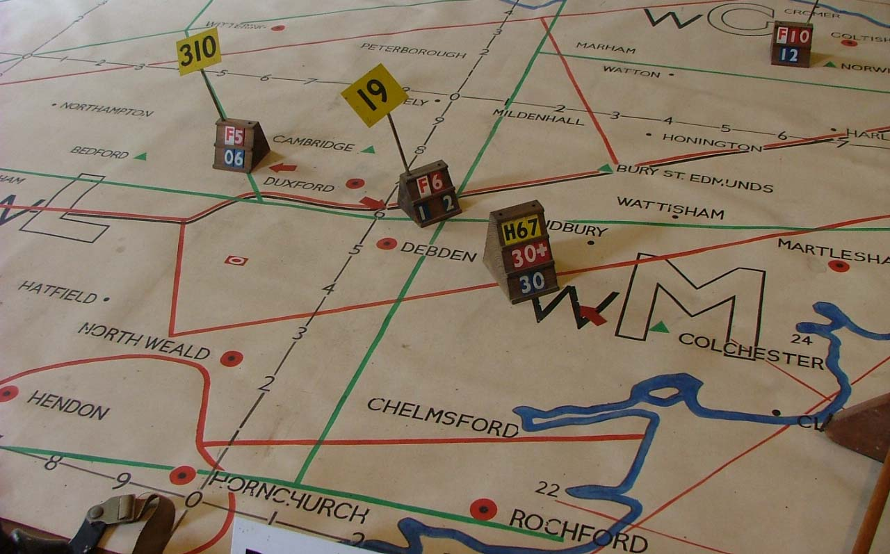 a photo of a Battle of Britain plotting table with counters and a map showing airfields in Norfolk and Essex