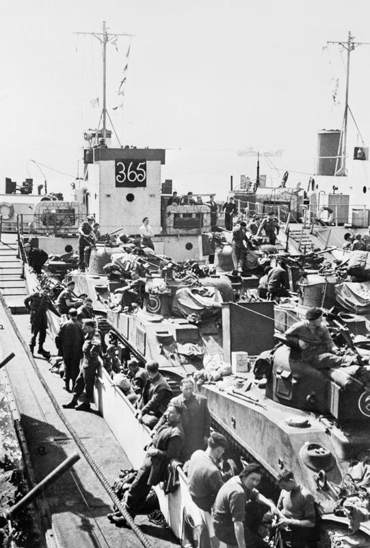 a balc and white photo of troops and tanks on a dockside