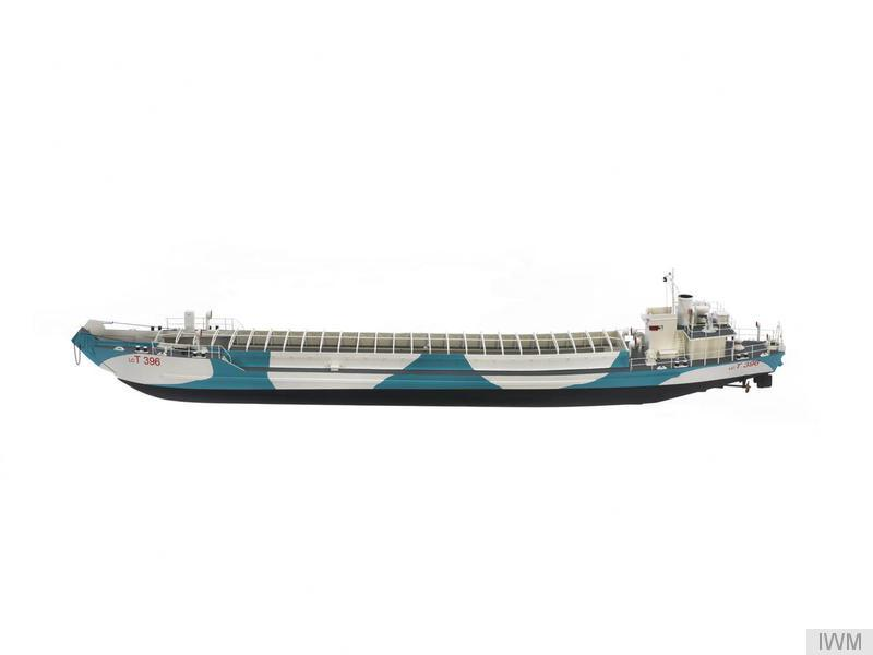 a side on view of a model of landing craft with light blue and grey camouflage