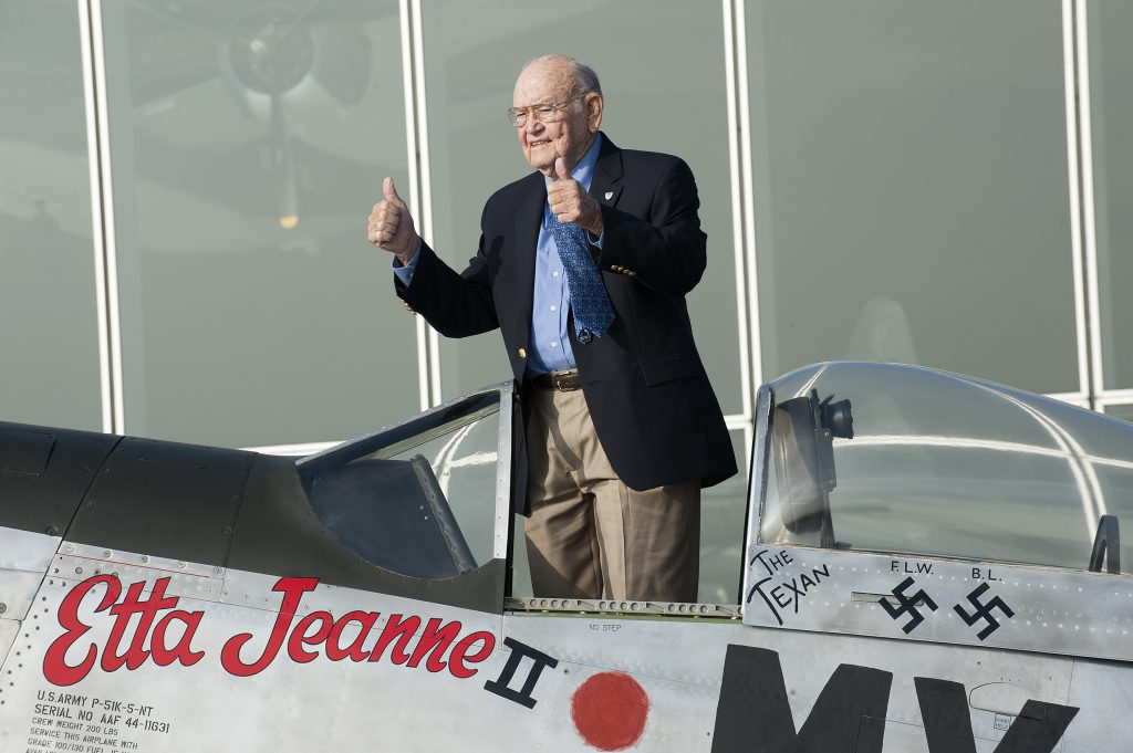 A photo of an elderly man standing in a cockpit